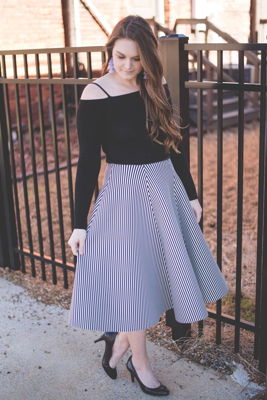 girl looking down in skirt and top with tassel earrings.
